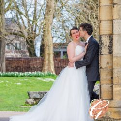 bride-and-groom-leaning-against-abbey-ruins-pillar-york-museum-gardens
