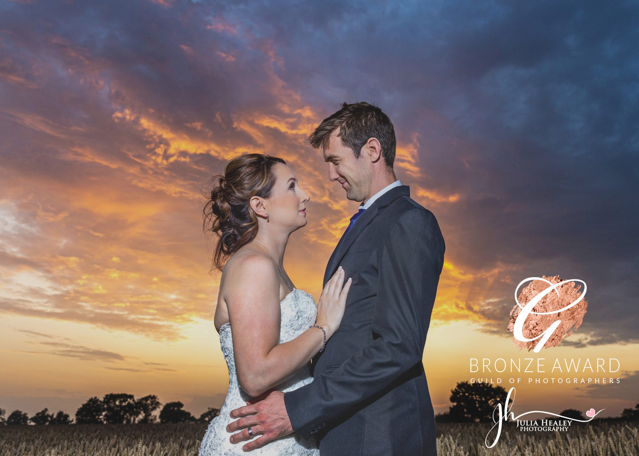 bride-and-groom-in-crop-field-looking-at-each-other-during-sunset