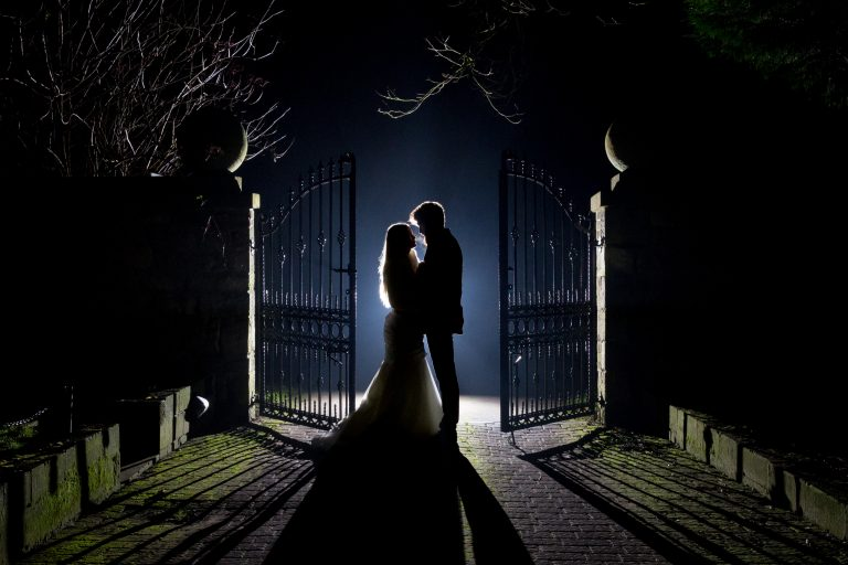 Silhouette-image-of-bride-and-groom-outside-venue-gates