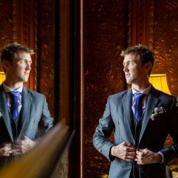 Groom-looking-into-mirror