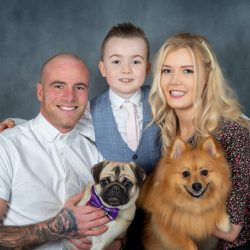 family-and-pug-and-pomeranian-against-studio-backdrop