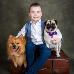 boy-with-pomeranian-and-pug-sat-on-suitcase-against-green-studio-backdrop