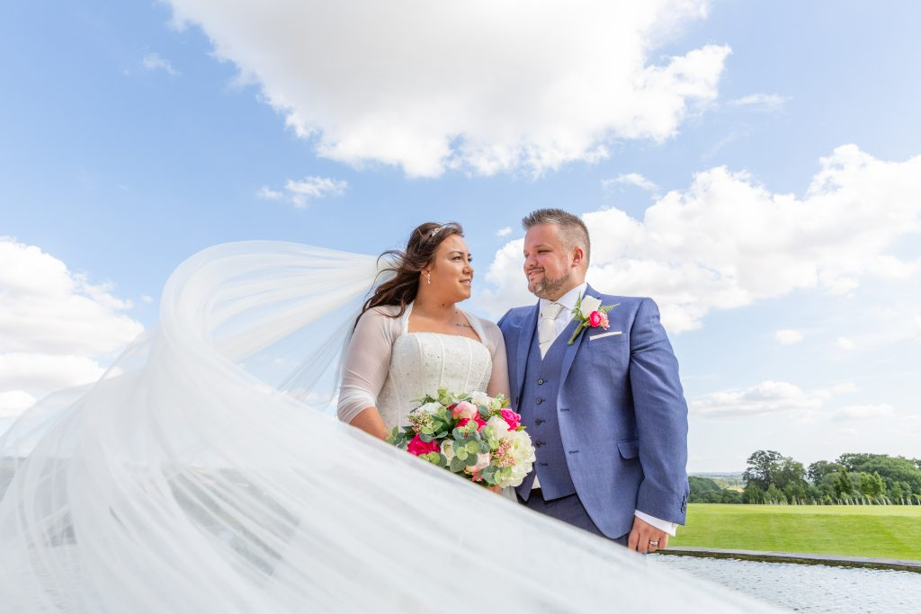 Kilnwick Percy Resort wedding photographer bride-and-groom-with-veil-sweeping-in-front-with-blue-sky-behind