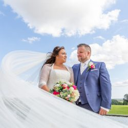 bride-and-groom-with-veil-sweeping-in-front-with-blue-sky-behind
