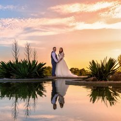bride-and-groom-in-sunset-reflection-in-pond