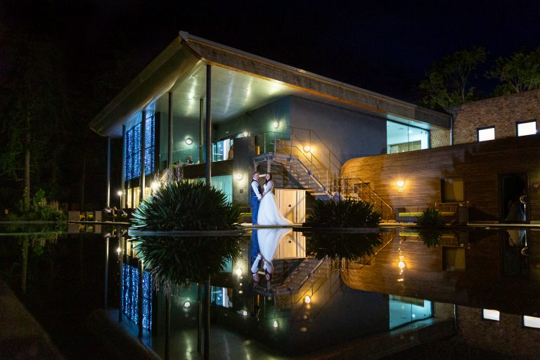 bride-and-groom-in-front-of-lit-up-venue-at-night