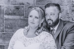 black and white image of bride and groom looking passed the camera