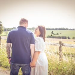 couple walking down country lane holding hands and laughing