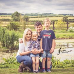 family in front of pond with view of countryside