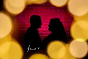 bride and groom silhouette against pink background with bokeh lights