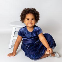 girl-in-blue-dress-sat-on-white-backgrounf