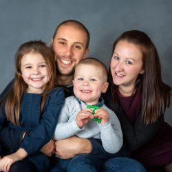 family-sat-against-grey-studio-fine-art-background